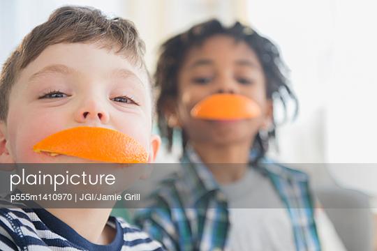 Boys biting orange slices - p555m1410970 by JGI/Jamie Grill