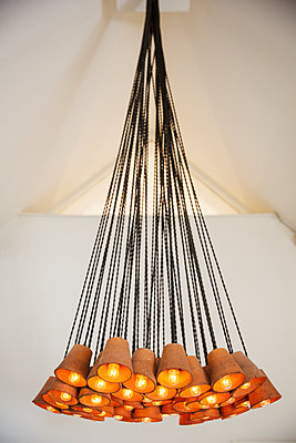 Close up of contemporary chandelier made out of terracotta flowerpots in a hotel.  - p1100m1450817 by Mint Images