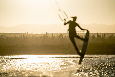 Young female athlete kiteboarding at sunset in La Ventana, Mexico - p1166m2157112 by Cavan Images