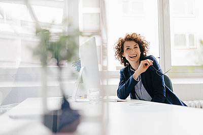 Businesswoman in office sitting at desk, laughing - p300m1469642 by Kniel Synnatzschke