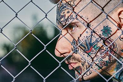 Tattooed face of young man behind fence - p300m1587010 von Zeljko Dangubic