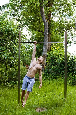 Athletic young man on high bar - p300m2023439 by Tom Chance