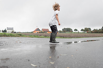 Boy jumping into a puddle - p300m2103253 by Ekaterina Yakunina