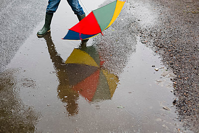 Little boy with umbrella and rubber boots standing in a puddle, partial view - p300m2219451 by Nicole Matthews