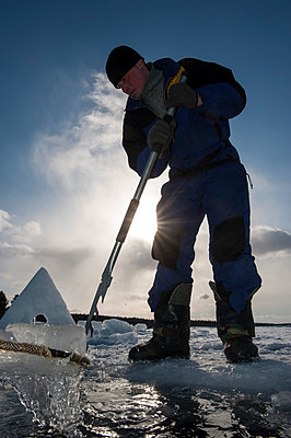 Russia, Arctic Circle Dive Centre, polar circle, White Sea, man preparing hole for ice diving - p300m975183f by Gerald Nowak