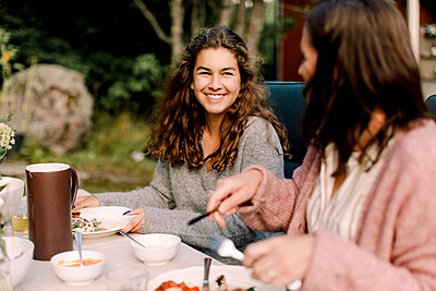 Smiling woman talking to daughter while sitting by dining table in backyard - p426m2227798 by Maskot