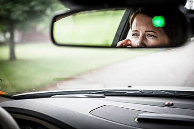 Reflection of woman in rear-view mirror of car - p426m858058f by Katja Kircher