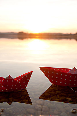 Zwei Papierschiffchen vor Sonnenuntergang - p533m1451902 von Böhm Monika