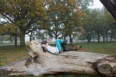 Young girl relaxing on tree stump in forest - p924m1094757f by Kaori Ando