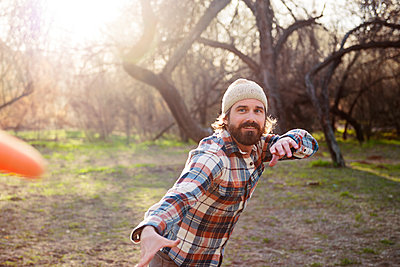 Portrait of happy man playing in forest - p1166m1142975 by Cavan Images