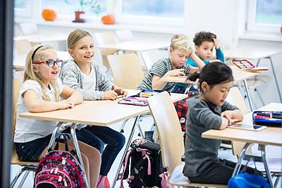 Pupils sitting at desks in class - p300m2004797 by Fotoagentur WESTEND61