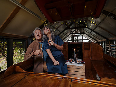 Senior couple having a candlelight dinner on a boat in boathouse - p300m2154977 von Gustafsson