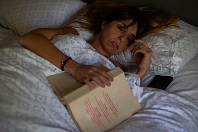 Woman asleep after reading a book in the bed - p300m2156755 by Veam