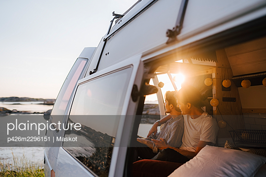 Gay couple spending leisure time in camping van at lakeshore - p426m2296151 by Maskot