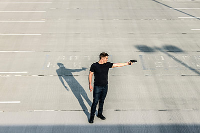 Armed man standing on parking deck - p1019m1424618 by Stephen Carroll