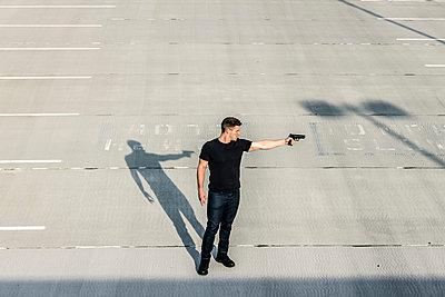 Mann mit Pistole auf einem Parkdeck - p1019m1424618 von Stephen Carroll