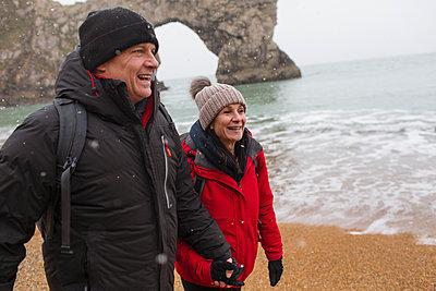 Happy couple in warm clothing walking on snowy ocean beach - p1023m2024326 by Sam Edwards