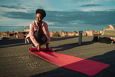Young female folding exercise mat on rooftop during sunrise - p426m2233501 by Maskot