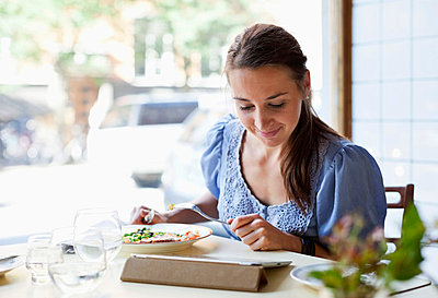 Young woman having meal while using digital tablet at restaurant table - p426m747380f by Maskot