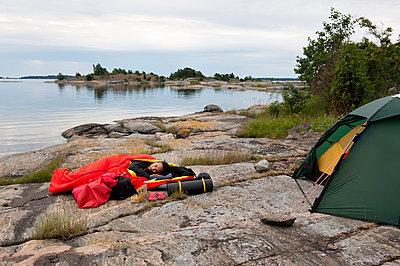 Woman camping on seashore - p575m1074567f by Fredrik Schlyter