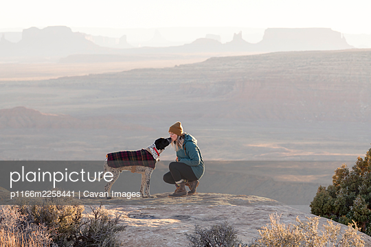 Young woman kissing dog on mountain peak at desert during vacation - p1166m2258441 by Cavan Images