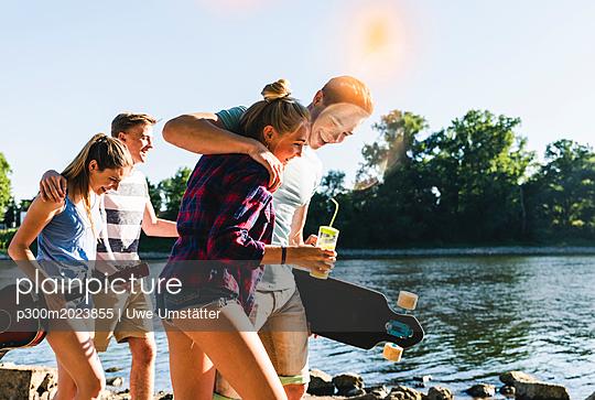 Group of happy friends walking at the riverside - p300m2023855 von Uwe Umstätter