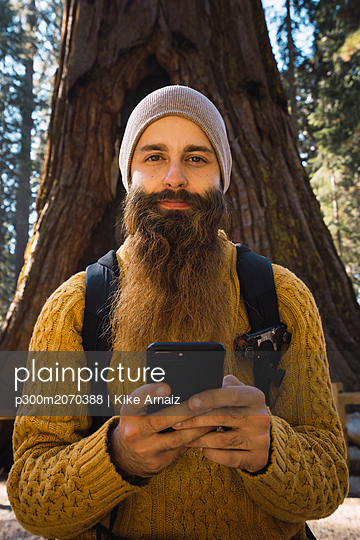 USA, California, Yosemite National Park, Mariposa, portrait of bearded man with cell phone at sequoia tree - p300m2070388 by Kike Arnaiz