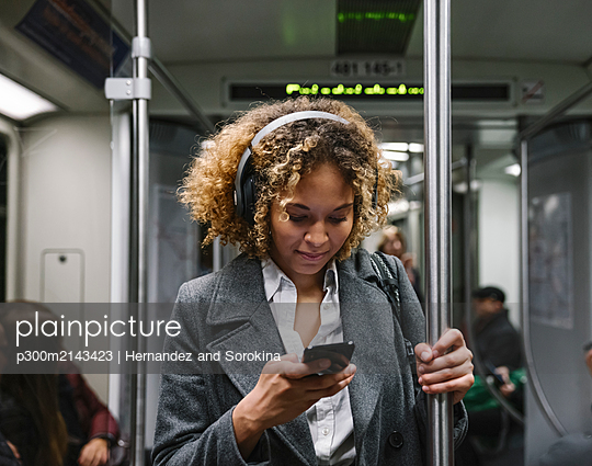 Woman using smartphone on a subway - p300m2143423 by Hernandez and Sorokina