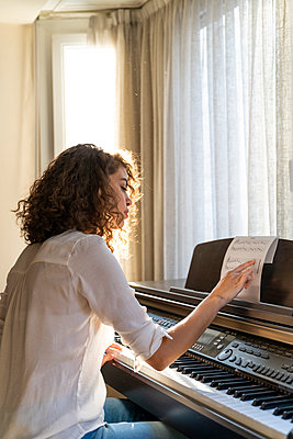 Woman playing piano at home - p300m2131683 by VITTA GALLERY