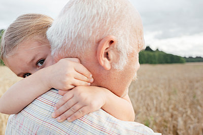 Granddaughter hugging her grandfather outdoors - p300m2143869 by Ekaterina Yakunina