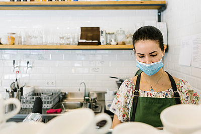 Woman wearing face mask while working in kitchen at coffee shop - p300m2227334 by Xavier Lorenzo