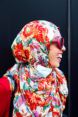 Cheerful woman in floral hijab against black wall during COVID-19 - p300m2240876 by Jose Luis CARRASCOSA