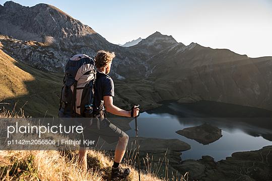 Junger Mann genießt Blick auf Bergsee - p1142m2056506 von Runar Lind