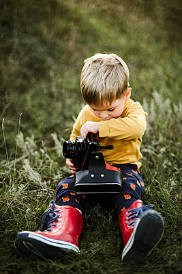 Boy  with camera while sitting on grassy field - p1166m2095998 by Cavan Images