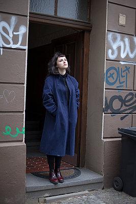 Junge Frau in Türrahmen - p1429m2021261 von Eva-Marlene Etzel
