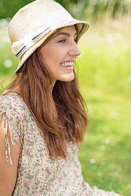 Young woman in summer hat sitting in meadow, happy. - p1433m1585124 by Wolf Kettler