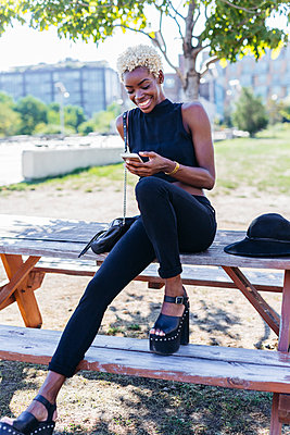 Smiling young woman sitting on wooden table looking on cell phone - p300m1206312 by Giorgio Fochesato