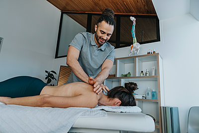 Smiling physiotherapist giving spine and upper back massage to female patient in medical practice - p300m2275987 by Mareen Fischinger
