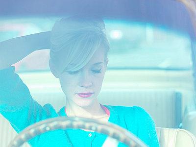 Woman fixing her hair in car - p429m663963 by Daniel Allan