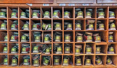 Bowling shoes stacked in cabinet - p555m1311530 by Spaces Images