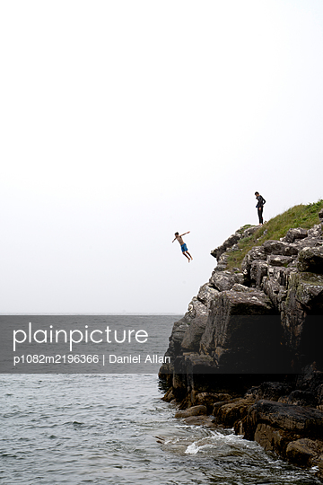 Teenage boys jumping from cliff into the sea - p1082m2196366 by Daniel Allan