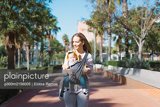 Mother walking with baby boy in sling outdoors - p300m2156005 by Eloisa Ramos