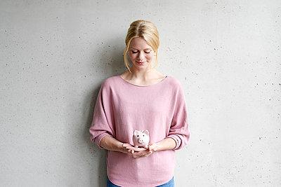 Junge Frau hält Sparschwein, Porträt - p1124m1511047 von Willing-Holtz