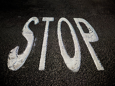 Stop sign painted on asphalt - p1462m1525588 by Massimo Giovannini