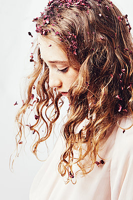 portrait of a young girl with flower petals - p1540m2211009 by Marie Tercafs