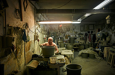 Potter in workshop working on large terracotta vase - p300m1191933 by Dirk Kittelberger