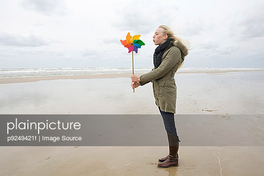 Young woman by sea with pinwheel - p9249421f by Image Source
