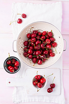Colander and bowls of cherries - p300m1157137 by Mandy Reschke