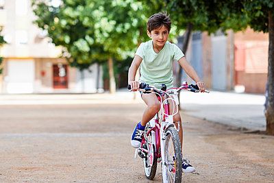Portrait of little girl riding bicycle - p300m2029406 von Javier Sánchez Mingorance