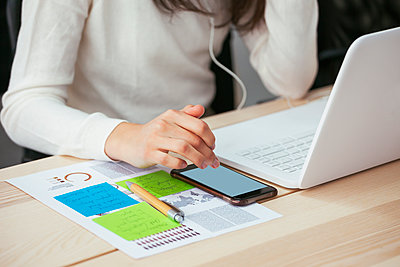 Close-up of woman with document, cell phone and laptop at desk in office - p300m2079204 by Bonninstudio